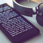 black smartphone near Skullcandy headphones