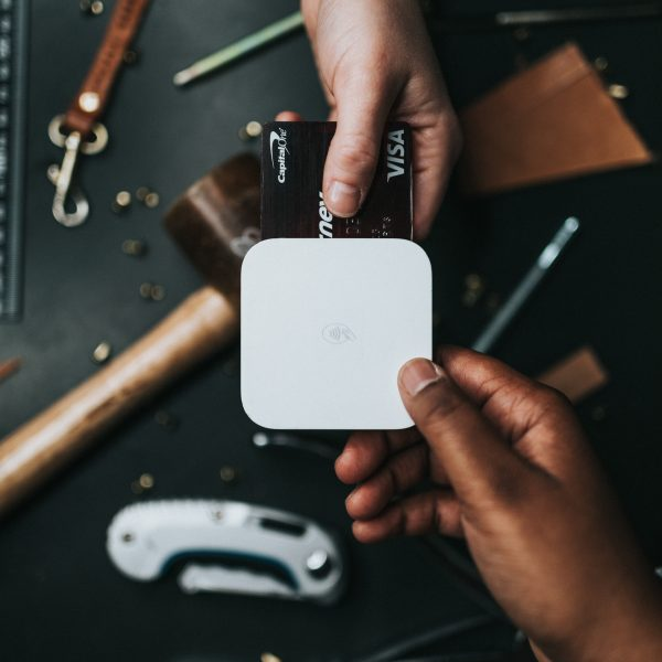 person holding Visa card and white device